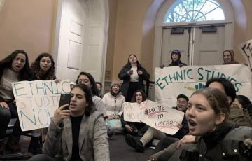 "A sit-in with students holding protest signs, ""Ethnic Studies Now"""